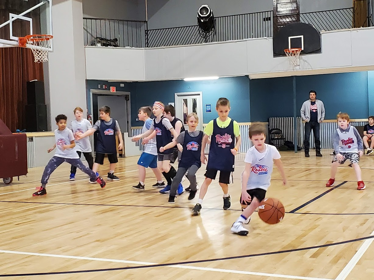 Young boy dribbling down the court