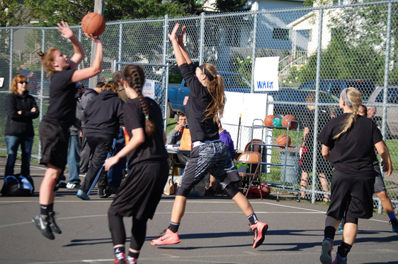 Girls rookie basketball team playing a game on an outdoor court