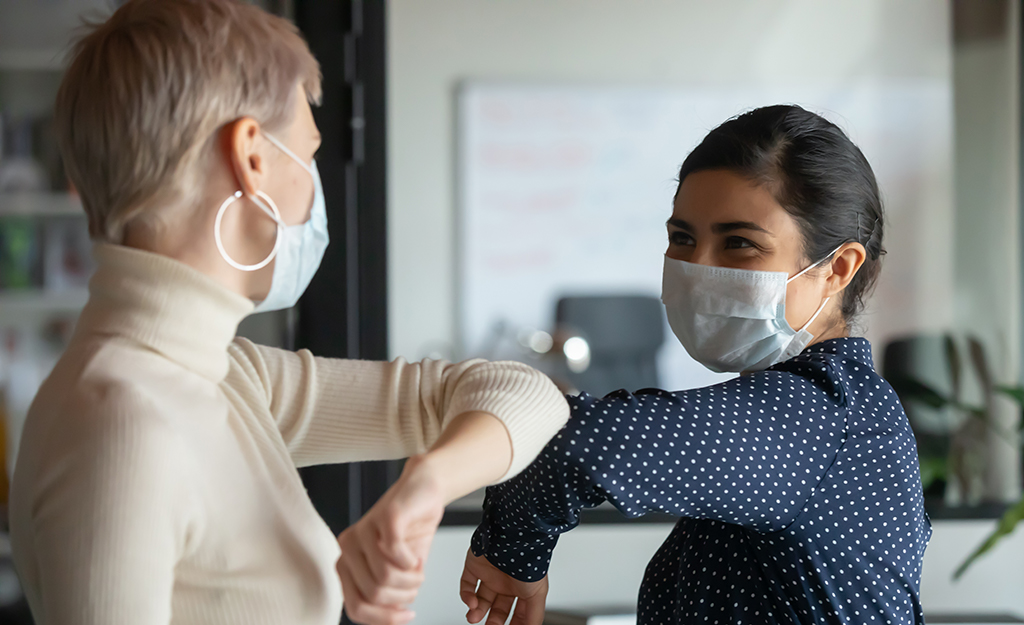 two women with masks and elbow bump greeting