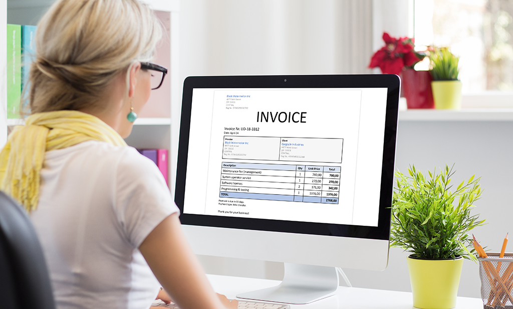 image of woman at computer screen with invoice on it