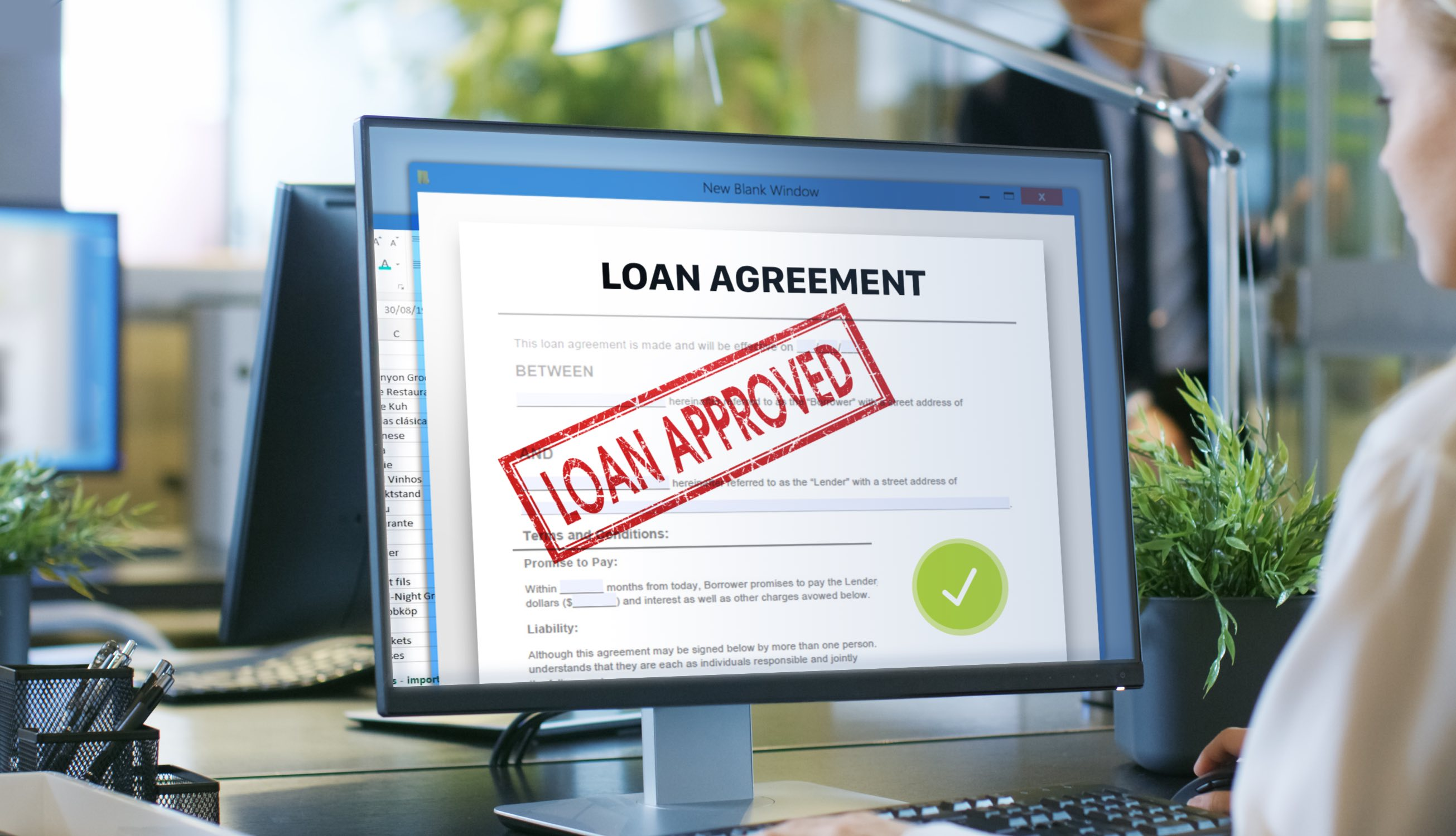 desktop with loan approved document on screen