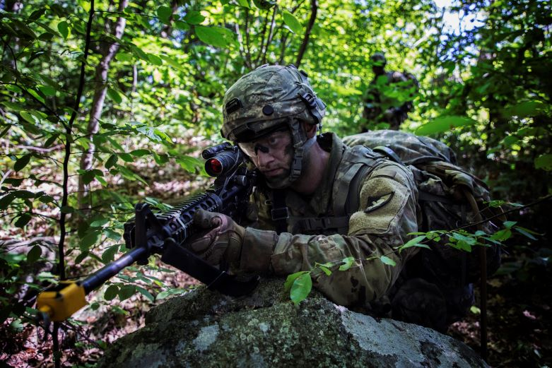 Male cadet holding rifle while leaning against large boulder during field training in a wooded area at Camp Buckner.