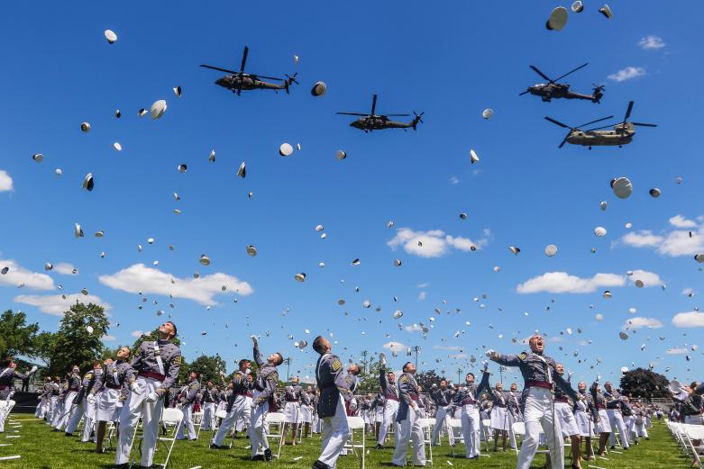 Cadets toss their hats during 2020 graduation ceremony with four helicopters flying over where cadets are standing.