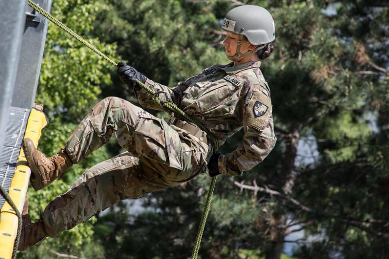 Female cadet repels down repel tower at West Point during air assault training.