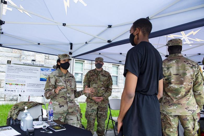 Cadet speaking with two officers at a booth during Branch Week at West Point.