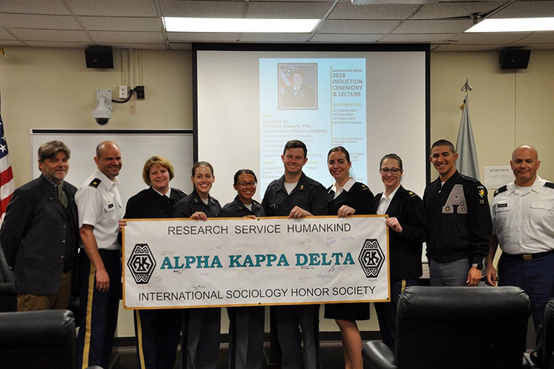 West Point's Alpha Kappa Delta (AKD) Sociology Honor Society holding the AKD banner in the Behavioral Science & Leadership conference room at West Point.
