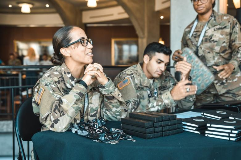 Female soldier and two West Point cadets welcome guests at conference while behind check in table.