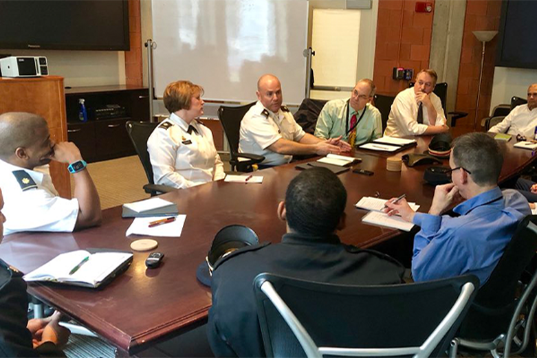 Brigadier General Cindy Jebb seated at large table with eight other members of the Dean's Diversity Committee; all meeting attendees are actively engaging in discussion.