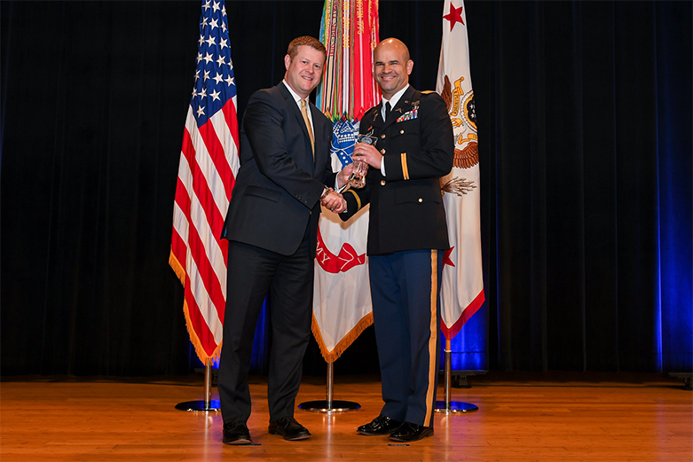 Major Jacob Absalon receiving Department of the Army Diversity & Leadership Award from ceremony host.