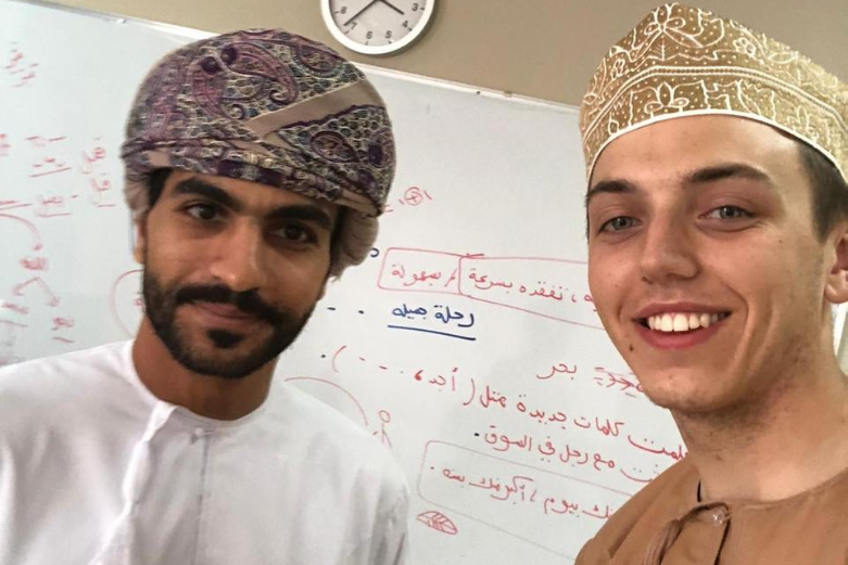 Cadet learning Arabic Script in Oman with an instructor in front of a white board