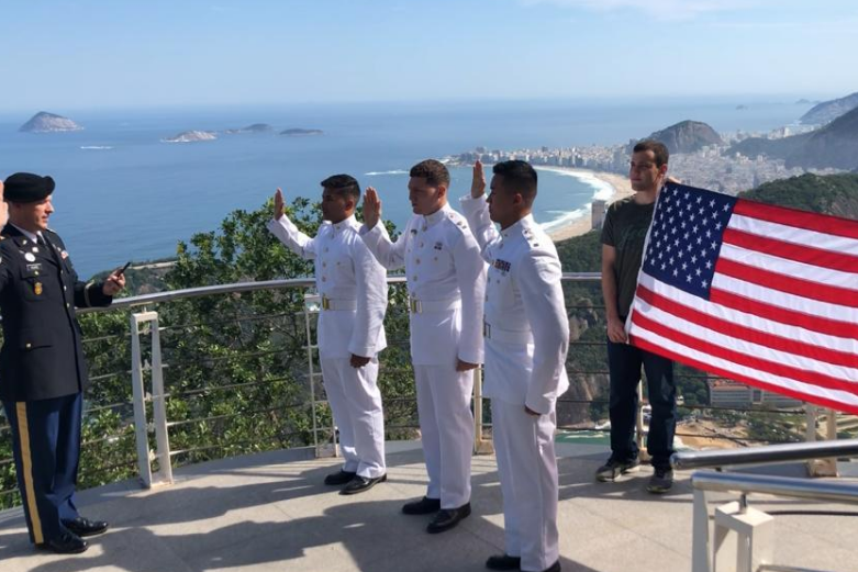 Cadets in white uniform taking oath of office with the river and an American flag behind them in Rio de Janeiro