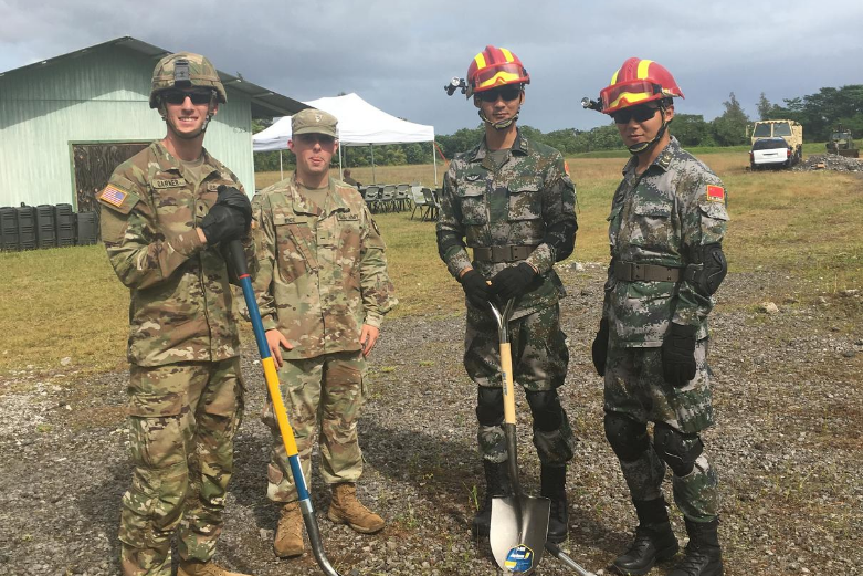 Two American cadets with two Taiwan cadets holding shovels in a field in Taiwan