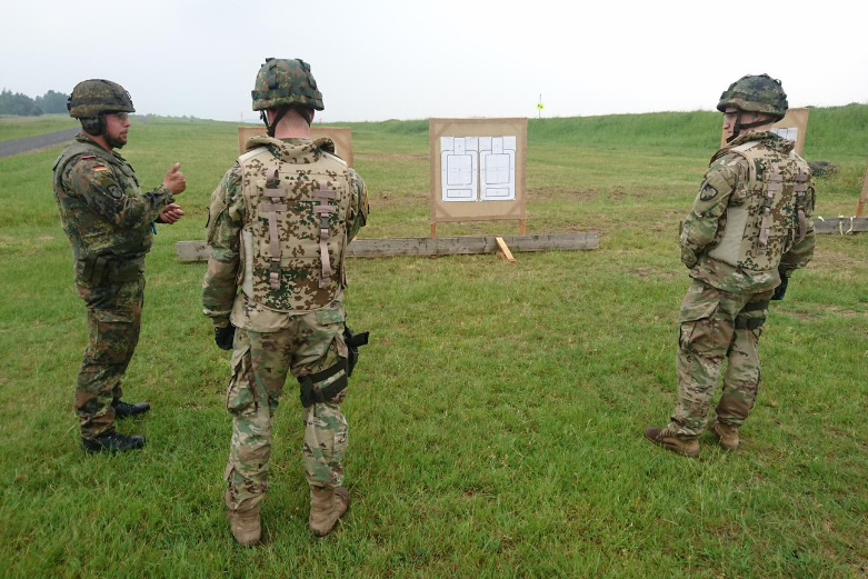 Two West Point cadets and one German soldier practice marksmanship in Germany on a firing range
