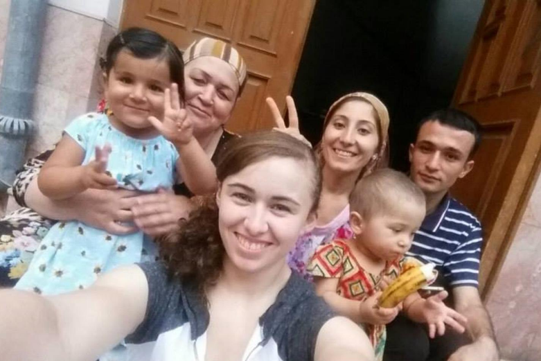 A cadet takes a selfie with their Persian host family on the steps of a house