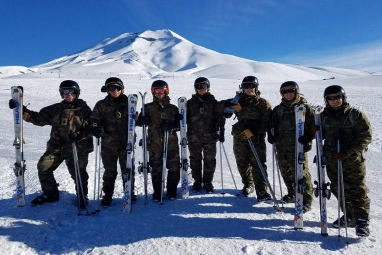 Seven cadets with skis stand for a photo on top of a snow capped mountain in Spain