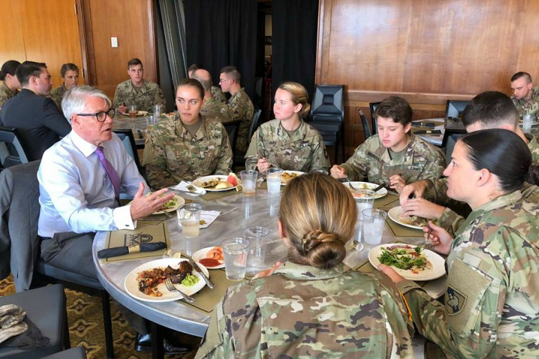 Cadets in camouflage uniforms dine around a table with a professor.
