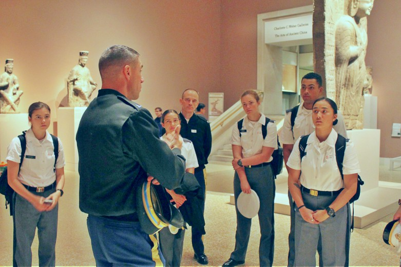 A history instructor speaks to students in white uniforms in a gallery filled with ancient marble statues.