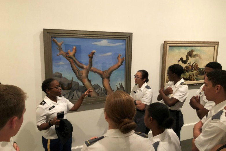A history instructor speaks to a group of cadets in white uniforms standing around a painting.