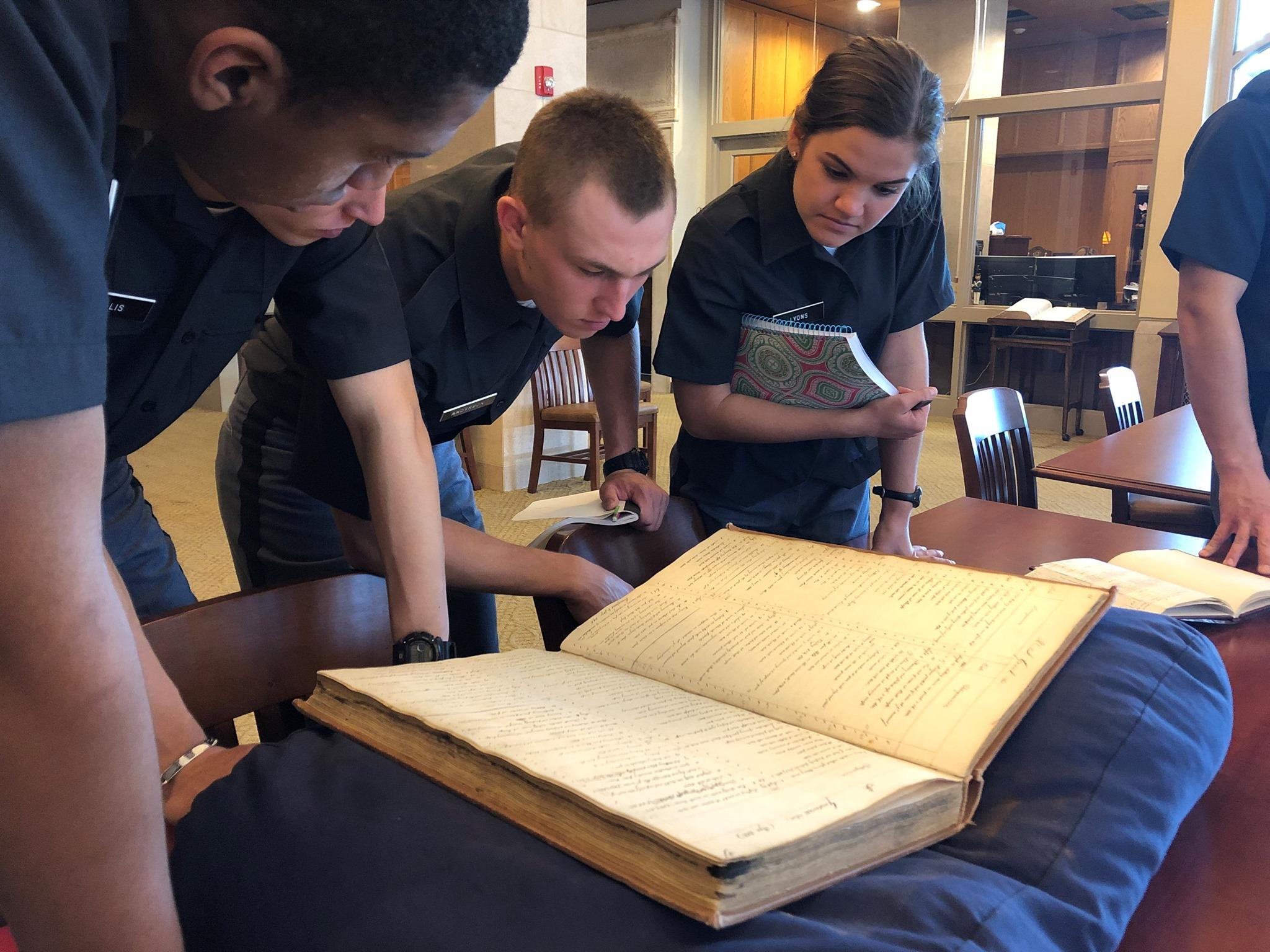 Students observe a large manuscript.