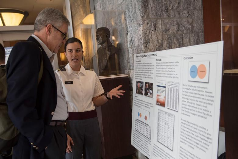 West Point cadet presenting her research on retired flag officer endorsements to a retired flag officer.