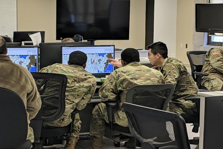 Cadets grouped together in front of a computer while using simulation software at the West Point Simulation Center.