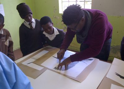 Students line up to help cut stencils for the art project - Pretoria