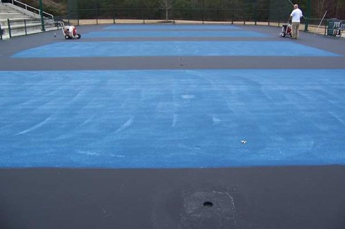 The blue acrylic surfacing is applied to the new 36' tennis court playing areas.