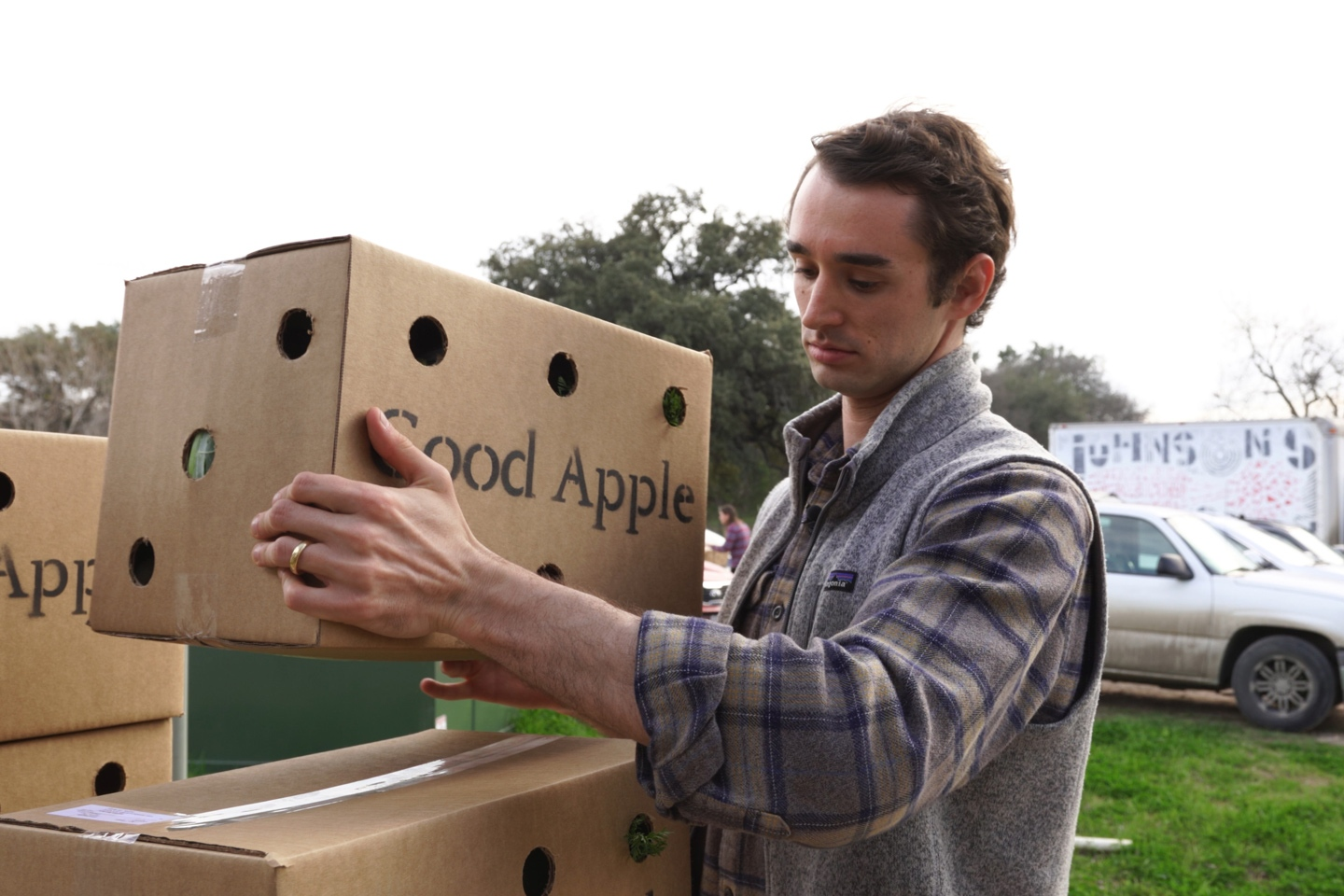 Zack Timmons, Good Apple's co-founder, loads boxes of produce for delivery.