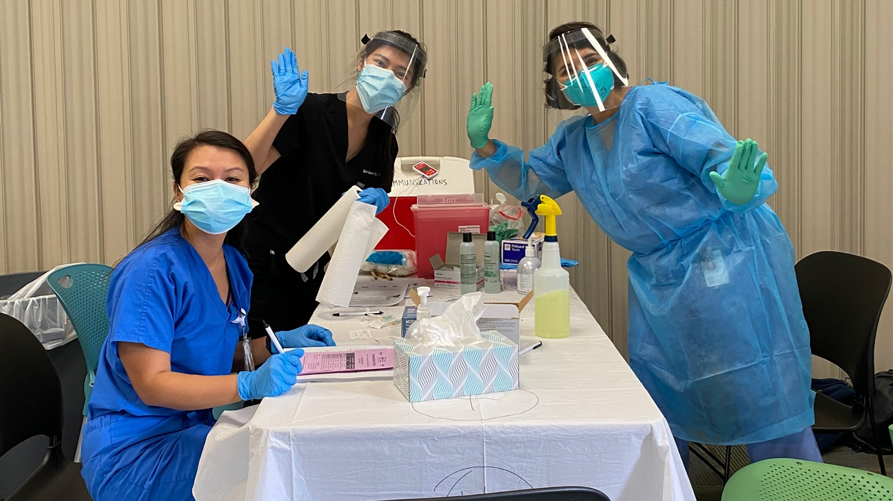Three female pediatrics residents at a table during their flu clinic.