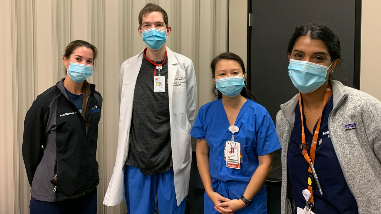 Four pediatrics residents and faculty in a group at their flu clinic.