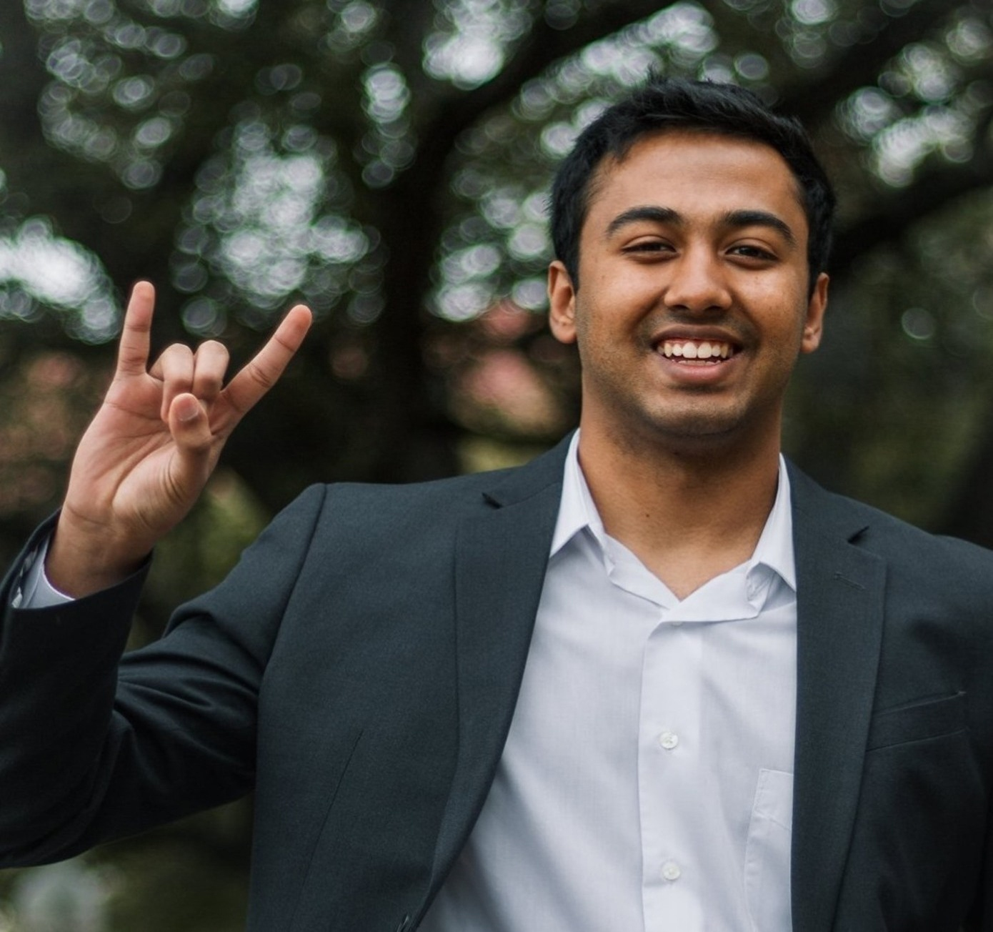 Undergraduate student Prajwal Gowda smiles and holds up the hook 'em hand sign.