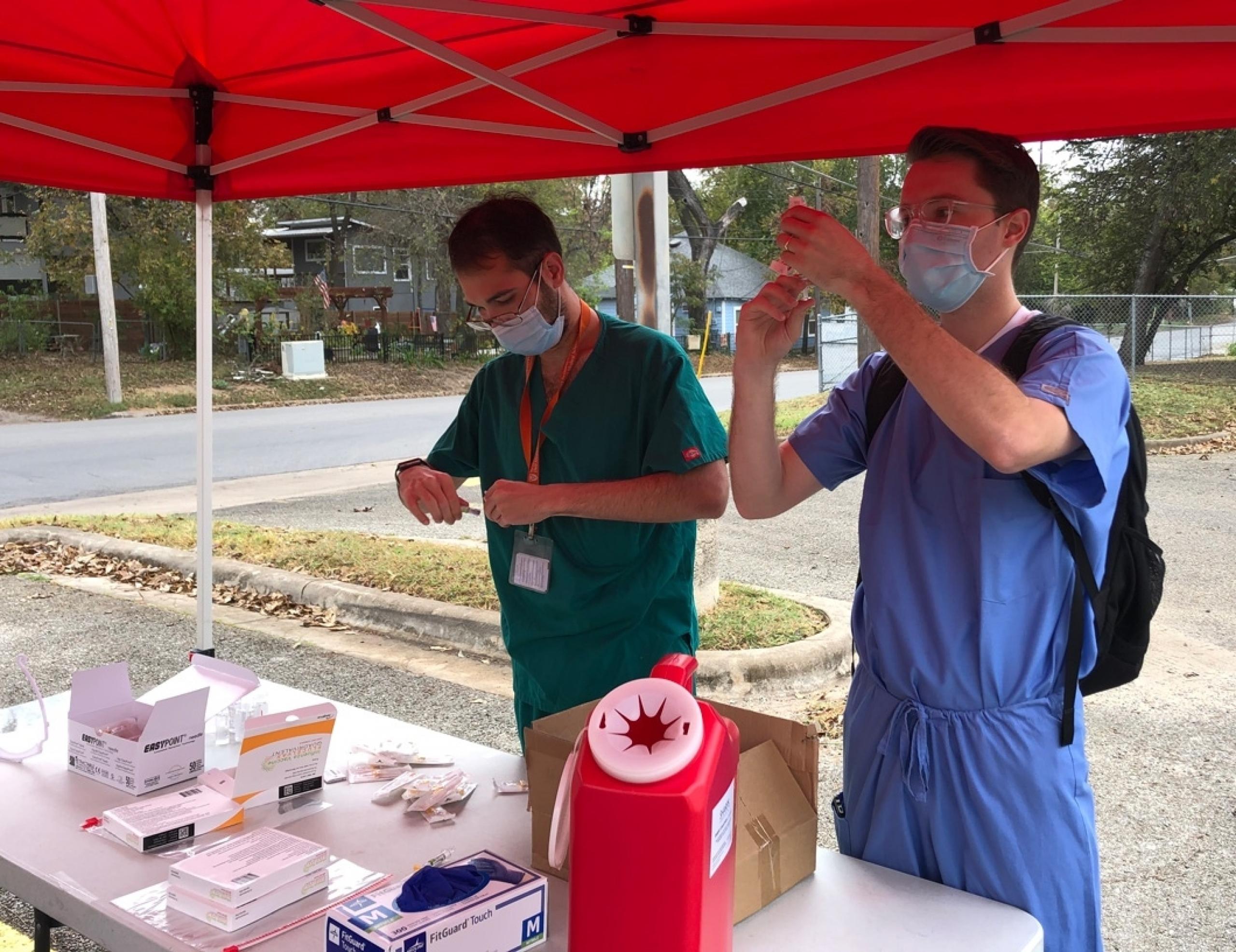 Two Dell Med students preparing flu shots.