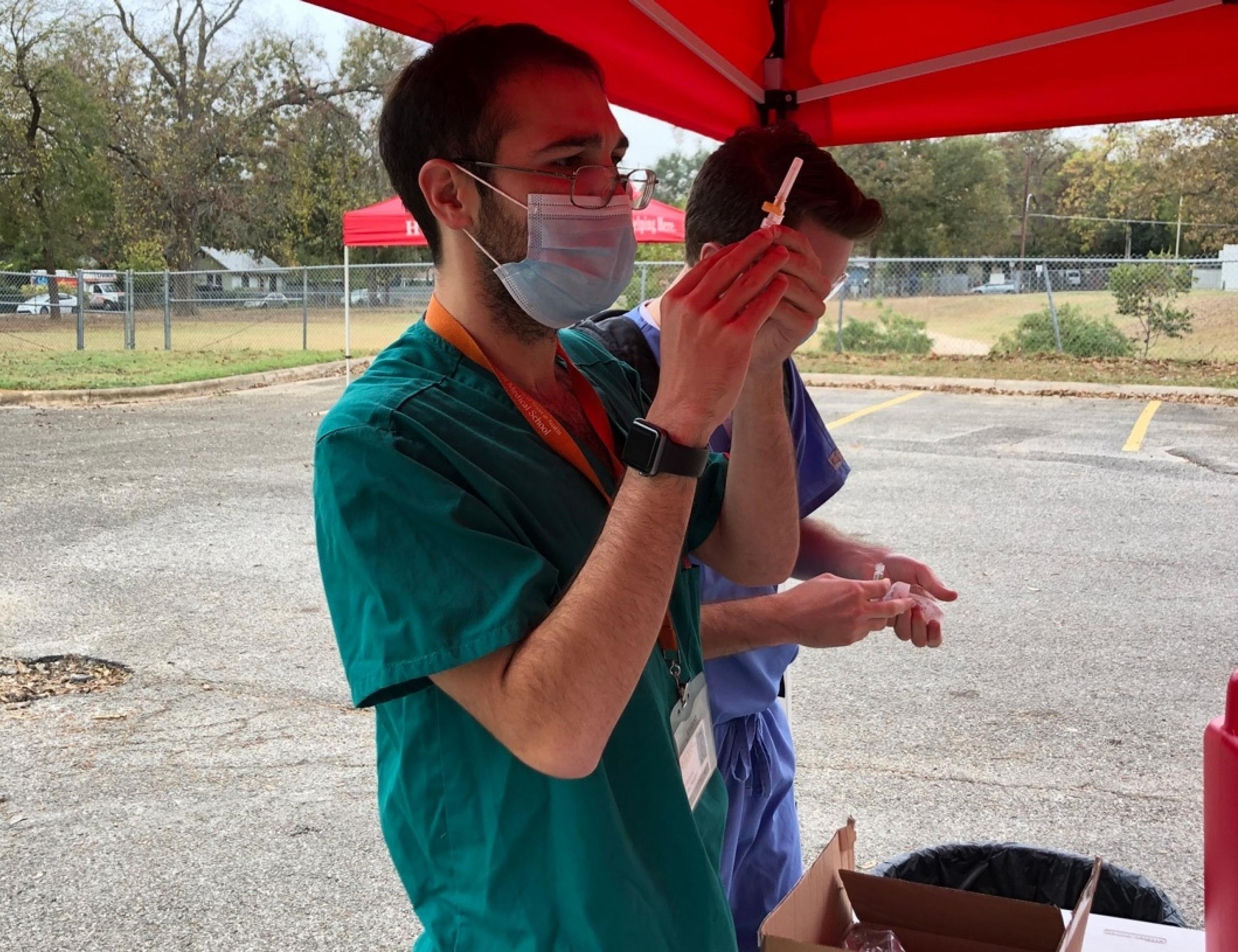 A Dell Med student preparing a flu shot.