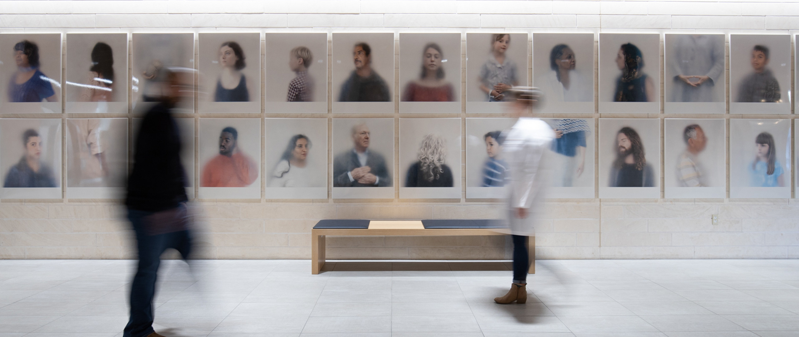 Two people walking in front of an art installation of portraits of faces in a row.