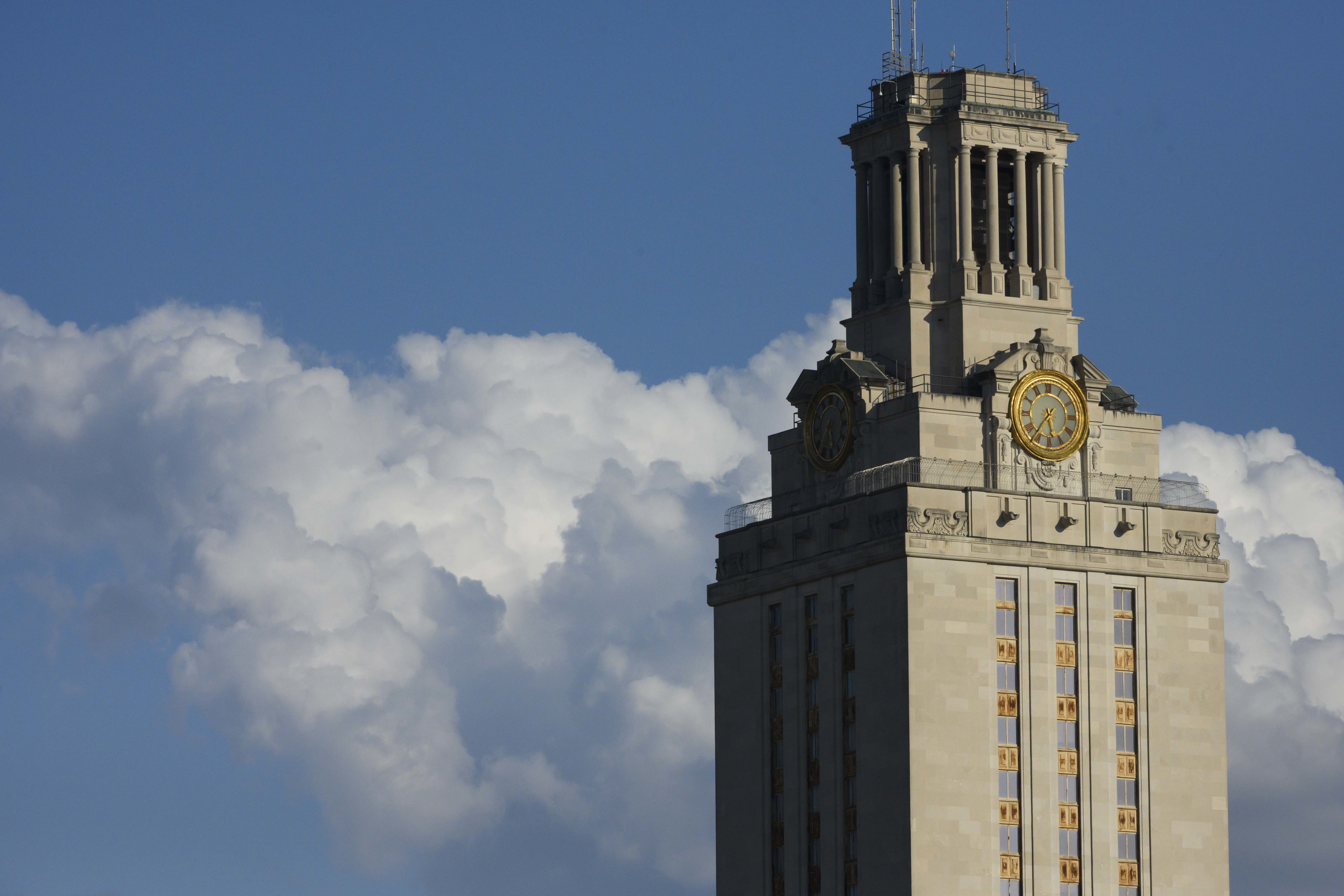 The UT Austin Tower with a blue sky and clouds in the background.