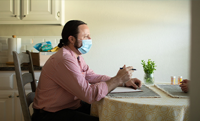 A community health worker having a discussion with an individual at a dinner table.