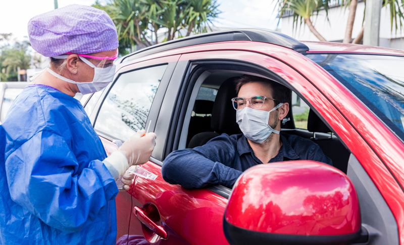 A health care worker testing a passenger in a car for COVID-19 at a drive-through testing site.