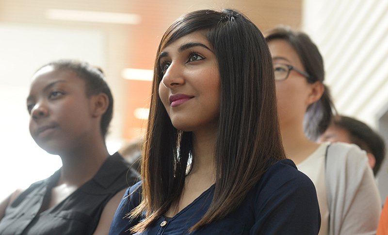 A student in a crowd listens to a speaker.