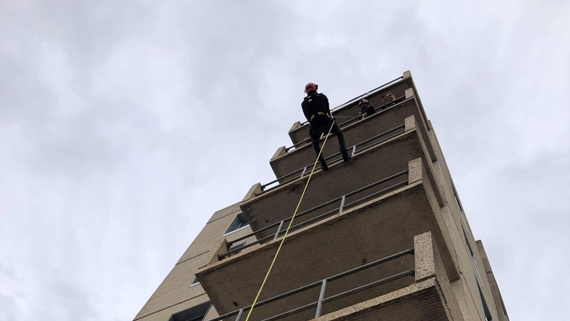 An EMS physician rappelling down the side of a building.