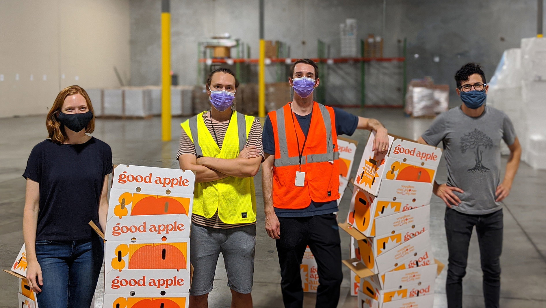 Four members of the Good Apple team standing in a warehouse with produce boxes.