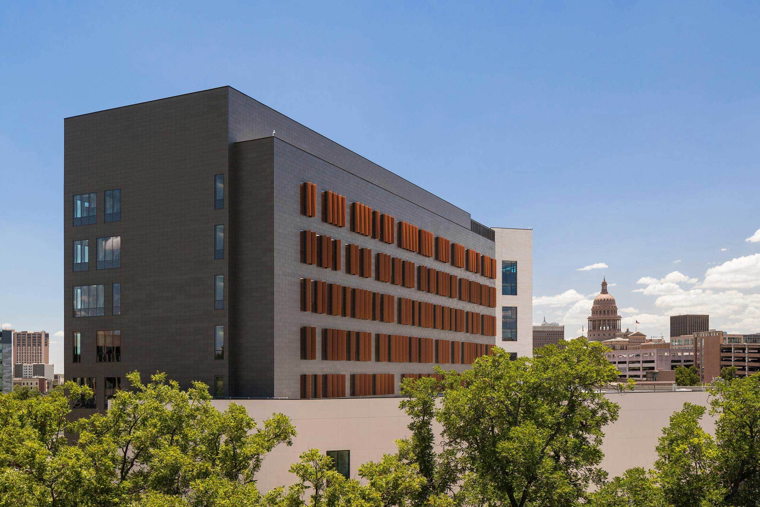 Dell Med Health Discovery Building with the Texas Capitol in the background.