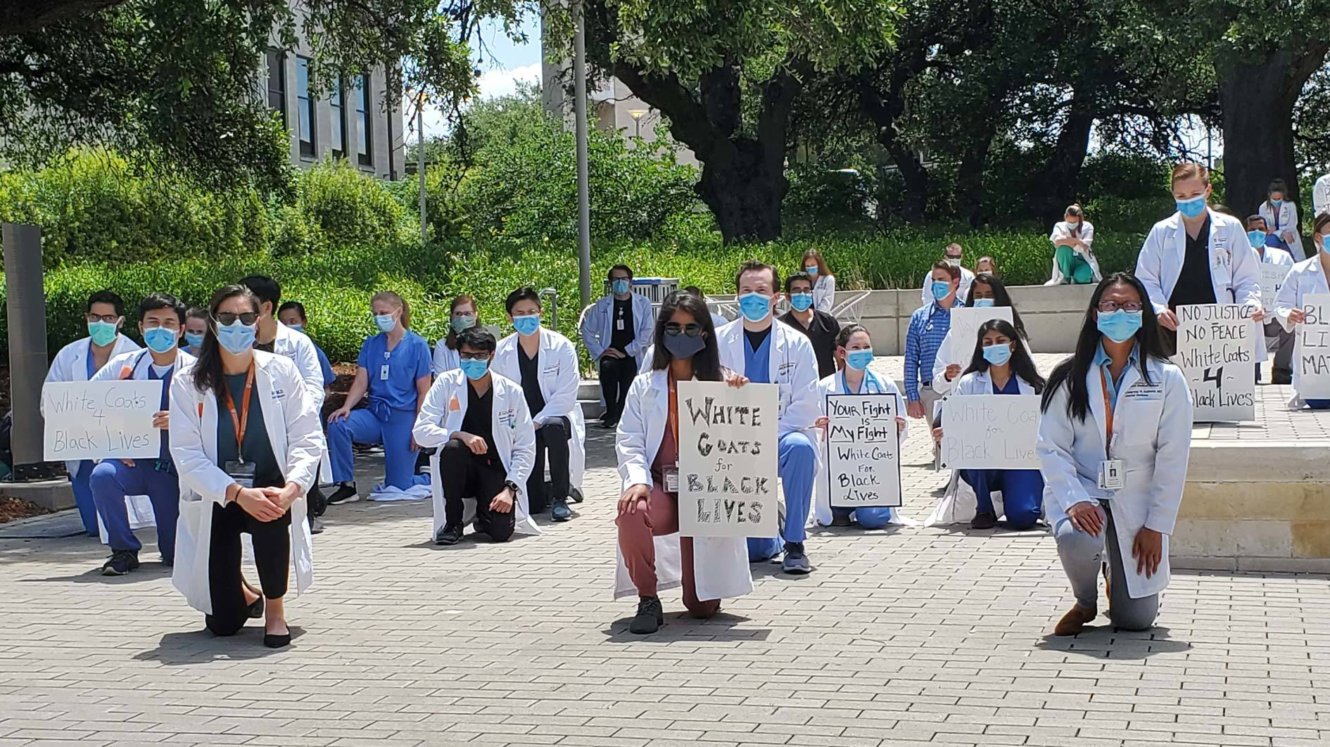 "Internal Medicine residents kneeling at a ""white coats for black lives"" protest."