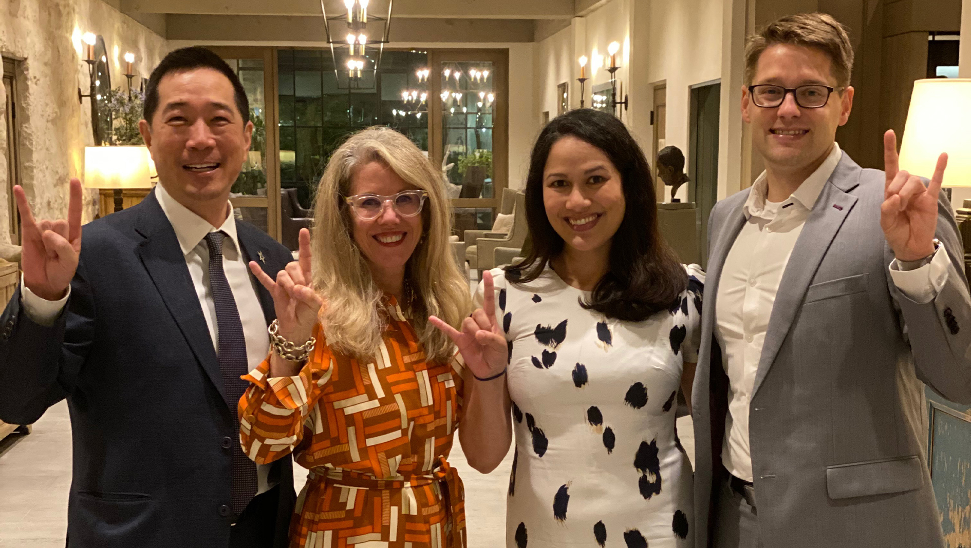 Four members of the Ophthalmology Residency posing in a group photo with the Hook 'em horns hand sign.