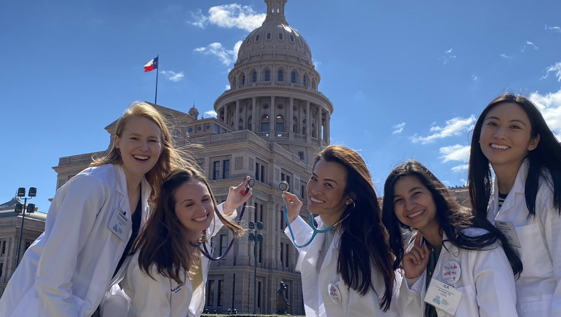 A group of female pediatrics residents in front of the Texas Capitol.