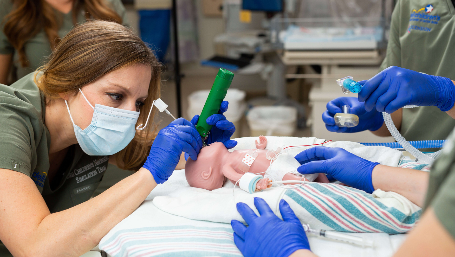 Medical professional simulating a neonatal medical exercise.