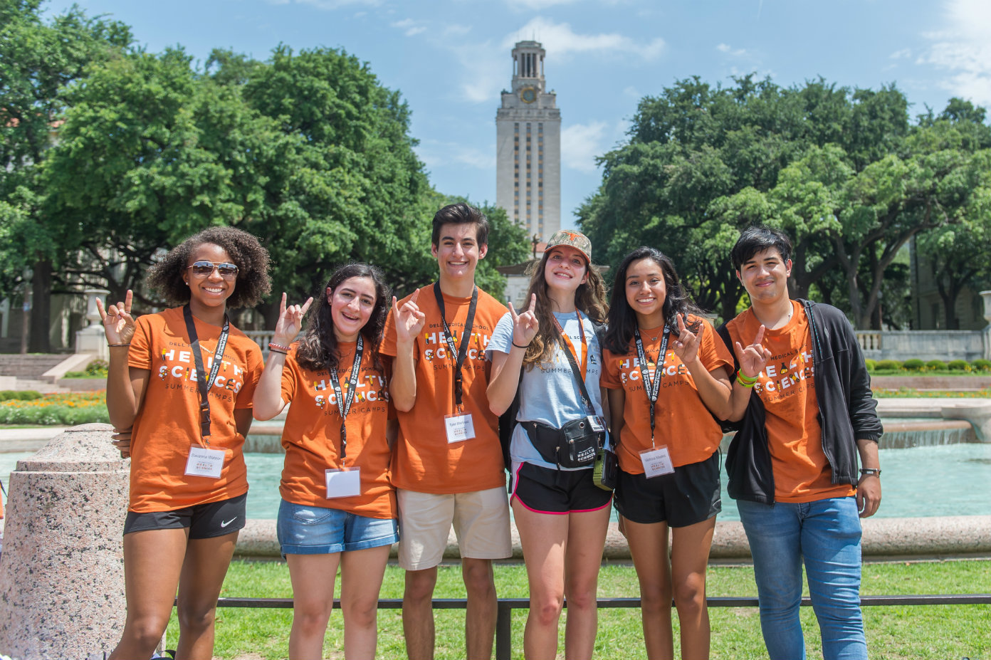 Summer camp participants pose for a photo in front of the UT Tower