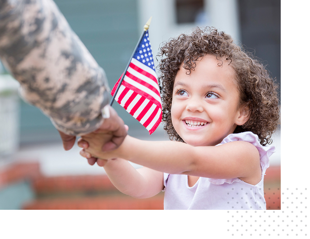 A young girl holds an American flag and greets her family member
