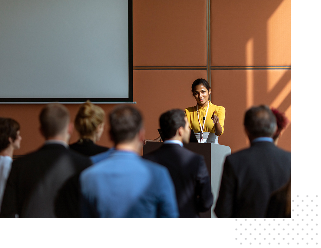 A woman giving a presentation in front of a crowd in a meeting room.