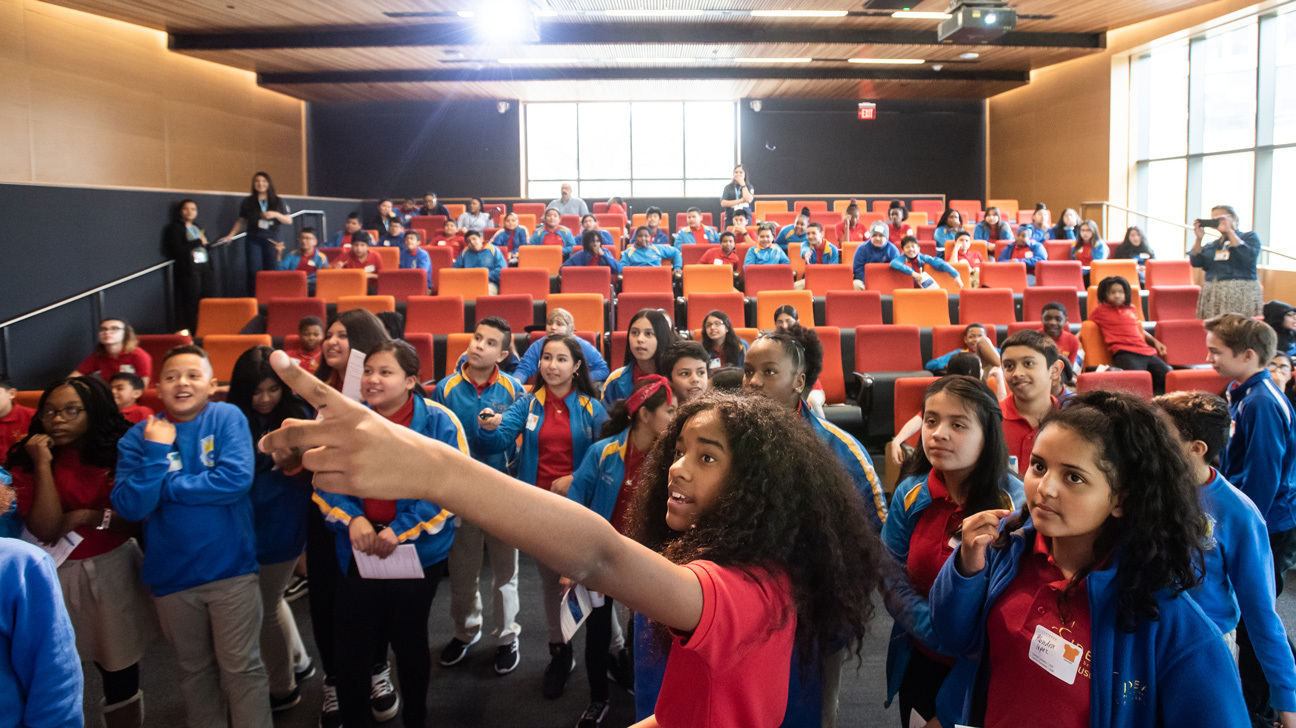 A female middle school student pointing at a projector screen while the rest of her class stands and sits behind her in an auditorium.