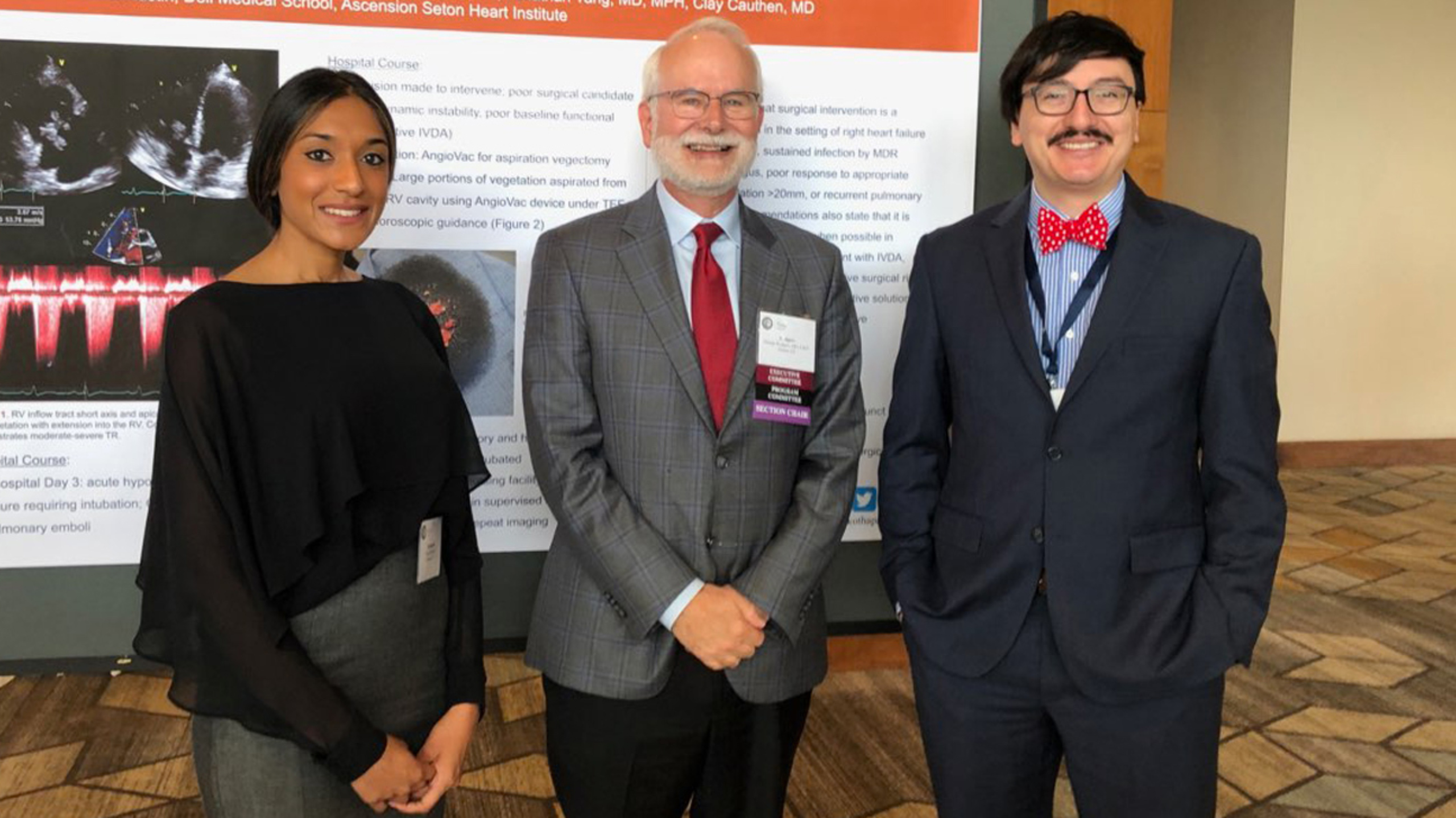 Two Cardiovascular Disease fellows and an adviser pose in front of a research poster at a conference.